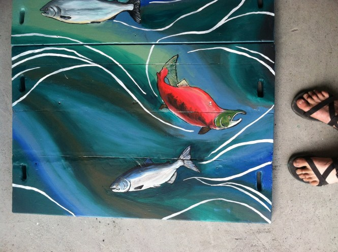 Sarah Glaser from Alaska of Sweet Roots Illustration paints raft for Kenai Riverdog company