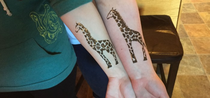 Sarah Glaser henna painting of matching giraffes during birthday party in Anchorage Alaska.